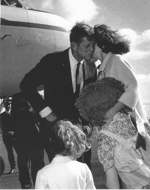 """Holding Caroline's oversized Raggedy Ann doll, """"Mother Annie,"""" Jackie kisses her husband farewell as he leaves in October 1960. Caroline waits her turn to say good-bye to Daddy."""