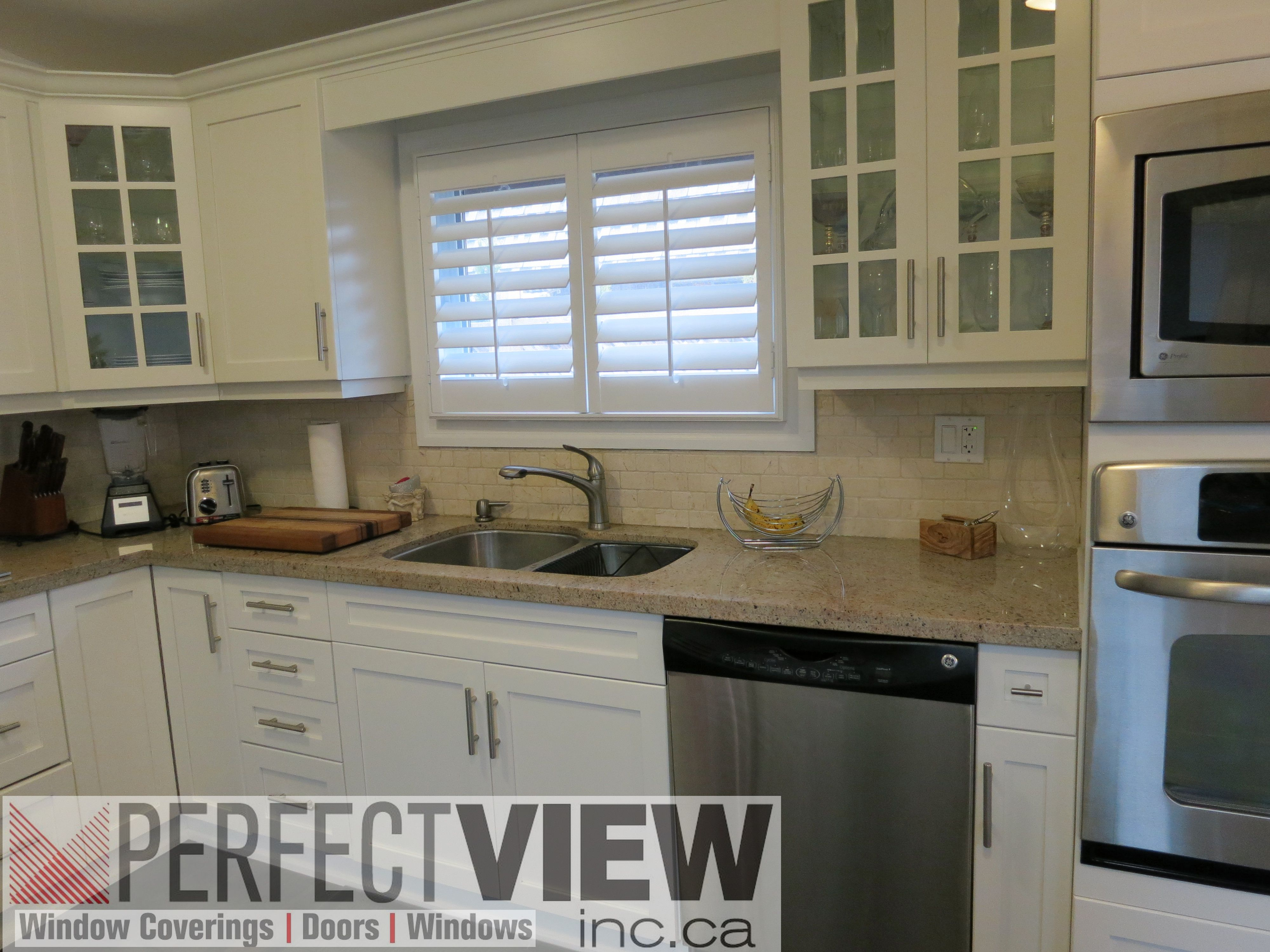Window coverings wood  white wood california shutters installed over a kitchen sink great