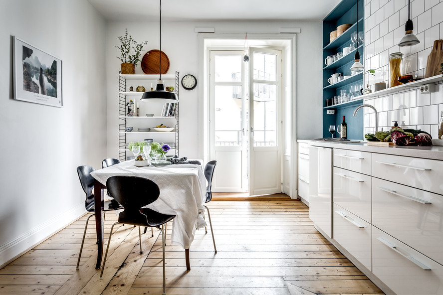 Big bright white kitchen with wooden floor and blue shelving #shelving #white #floor