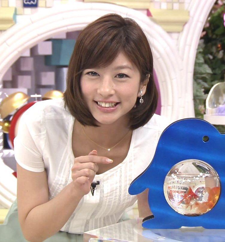 金魚鉢を指さし微笑むアナウンサー、生野陽子