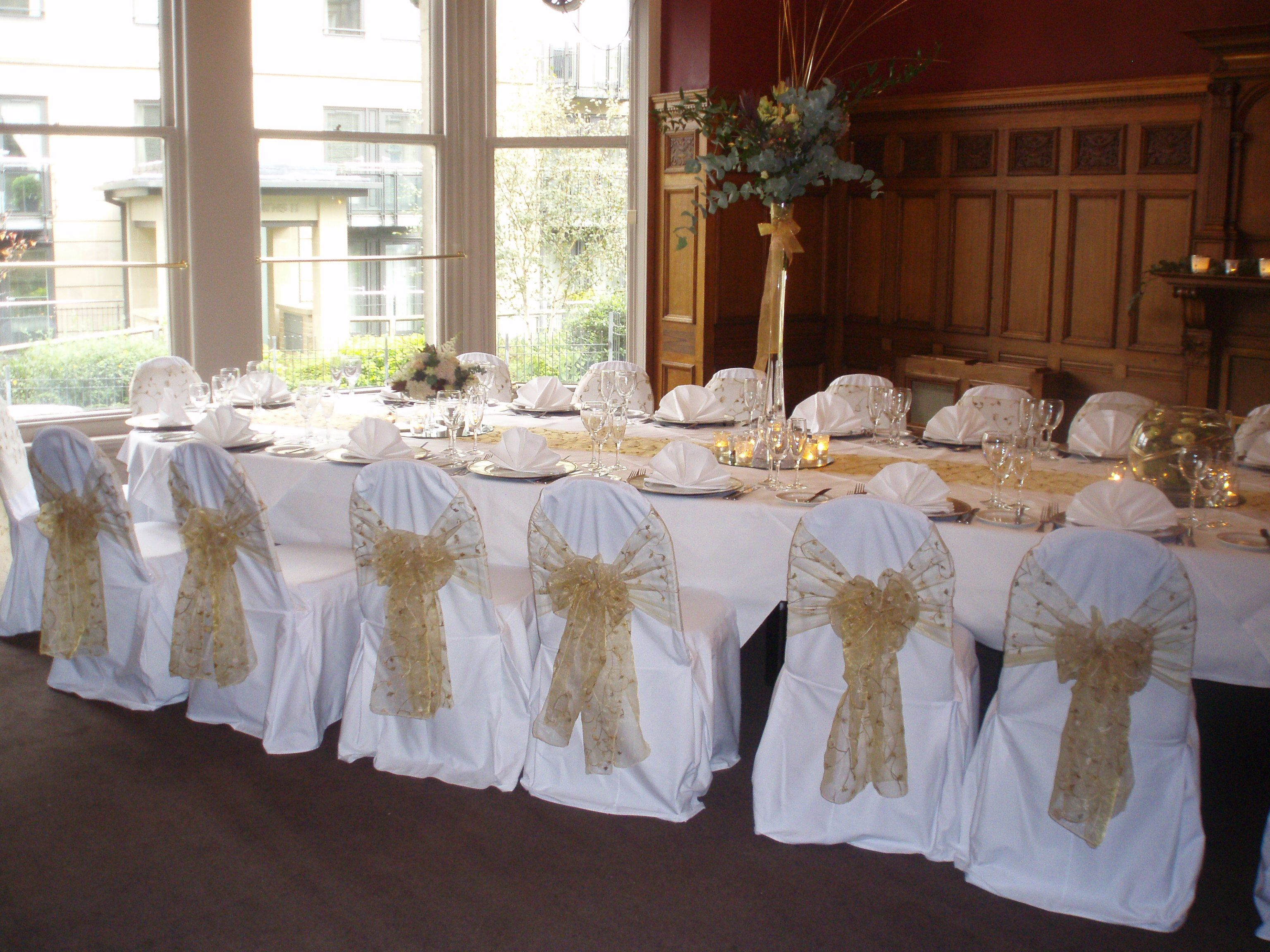 Gold embroidered organza sashes on white chair covers at The Crown