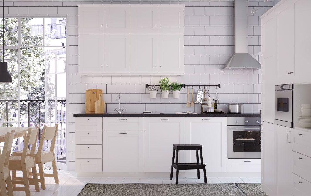 Eine mittelgrosse Küche mit SÄVEDAL Fronten in Weiss und schwarzen Arbeitsplatten Kitchen dreams