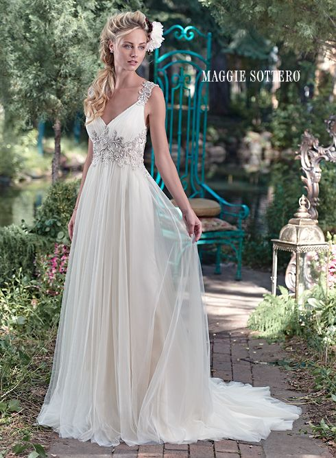 Kalisti wedding dress by Maggie Sottero | Romance is found in this stunning tulle sheath dress with plunging neckline and sparkling Swarovski crystal embellishment at the waist. Intricate patterns of beaded embroidery dance along the shoulder and lead to a dramatic illusion back. Finished with crystal button over zipper closure. Detachable tulle Watteau train sold separately.