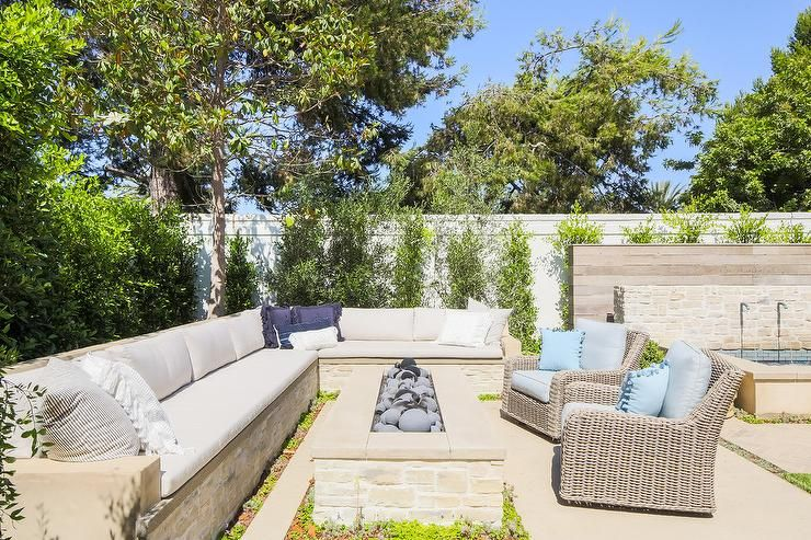 An L Shaped Stone Bench Sofa Is Topped With Light Gray Seat Cushions Accented With White And Blue Pillows Outdoor Fire Pit Outdoor Patio