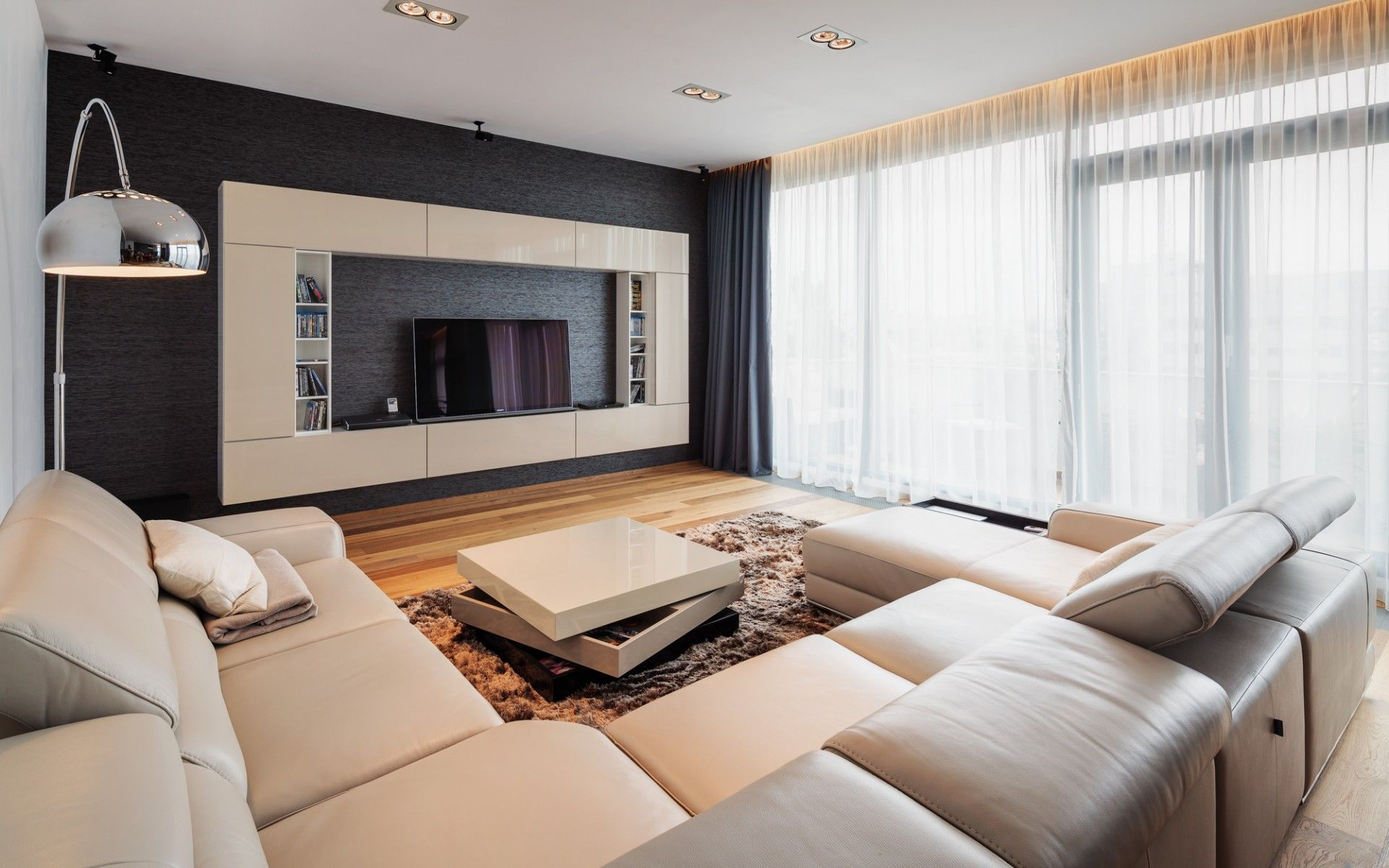 Wonderful Large Modern Tv Room Design With Cream Leather L Shaped Sofa Also Brown Laminated Wooden Floor