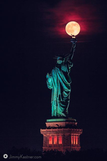 Rare summer solstice full moon balancing on the Statue of Liberty's torch