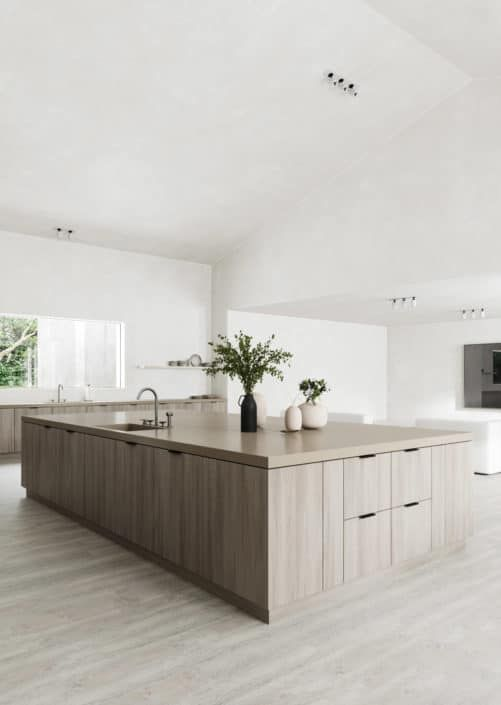 A kitchen in Minimalist Style. A large space affords this kitchen to do away with overhead cabinets, making everything within reach from the base drawers and keeping the space light and airy - so in the very spirit of the style. No clutter, neutral in scheme, bare window, few furnishings. #minimalist #kitchen