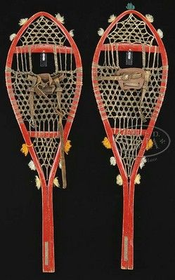 native american, America, Pair of Northeastern Woodlands Indian made snowshoes. The painted red wood frames having a rawhide gut weaving, leather strapping and decorative colored yarn [tassels].