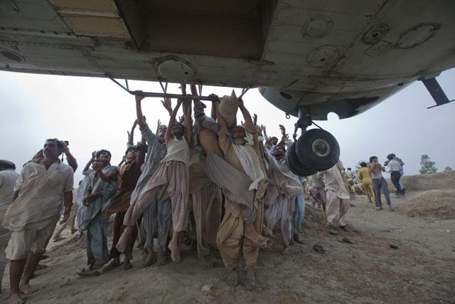 Marooned flood victims try to grab onto the side bars of a hovering army helicopter which arrived to distribute food supplies in the Muzaffargarh district of Pakistan's Punjab province, August 7, 2010. Adrees Latif. - Reuters