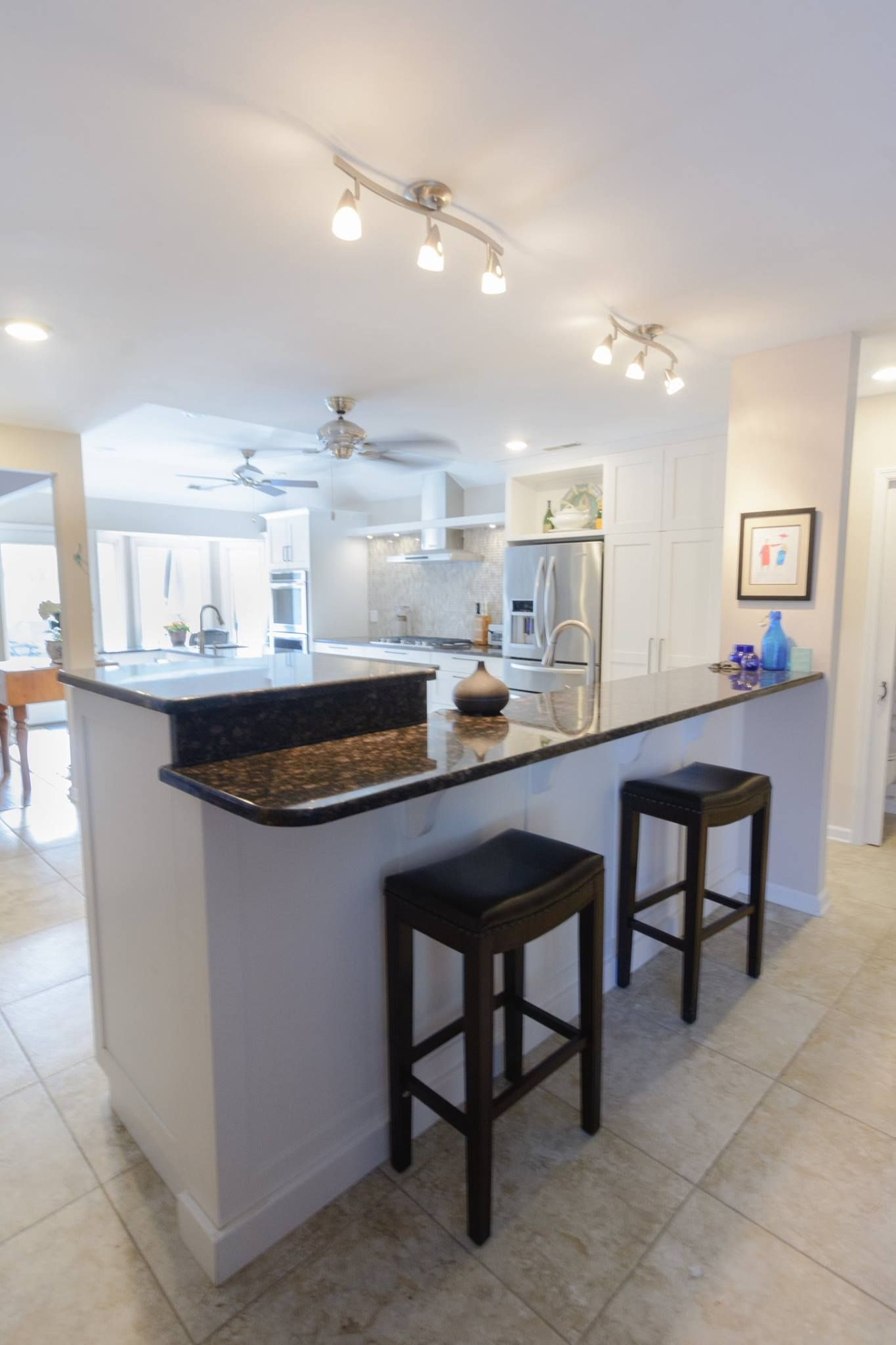 A spacious kitchen with fresh white cabinets and clean ...