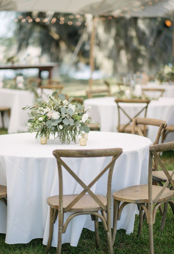 Silver and white flowers on a white table cloth with drift wood colored chairs for wedding reception