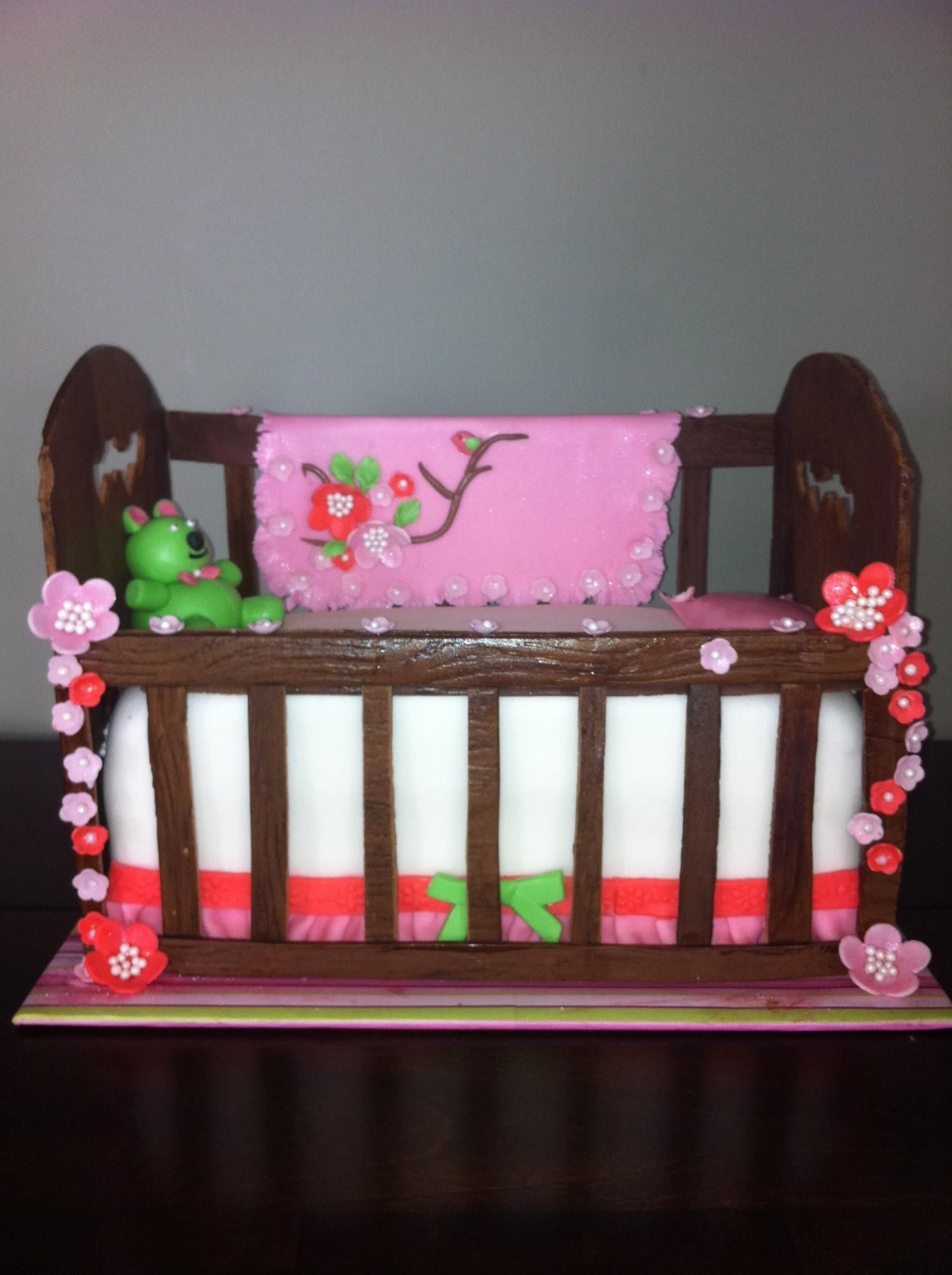 Chocolate Crib Cake - This cake was in honor of my best friend (her first grand child) and her daughter. I wanted something really special and after working day and night for 4 days straight, this is how it came out. Rails, head and foot boards are made of chocolate fondant and gum paste blend. I made these first so they had time to harden and I could carve cake to fit inside. I made individual slats which was a huge mistake. Next time I will cut slits out to make slats. Getting them to...