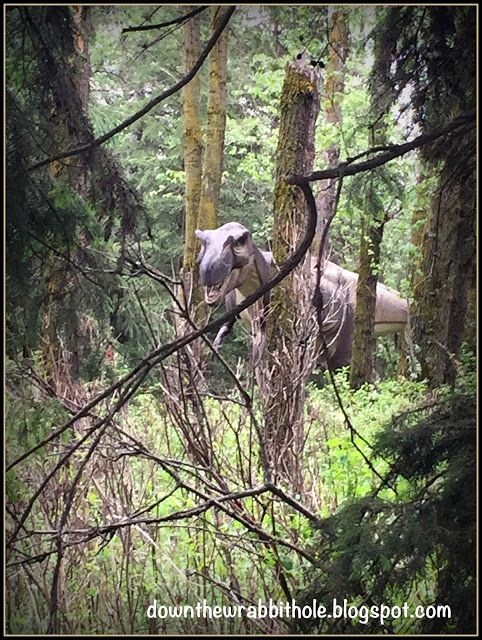 """An Albertasaurus peeks out from the trees at Edmonton's Jurassic Forest. Find out more at """"Down the Wrabbit Hole - The Travel Bucket List"""". Click the image for the blog post."""