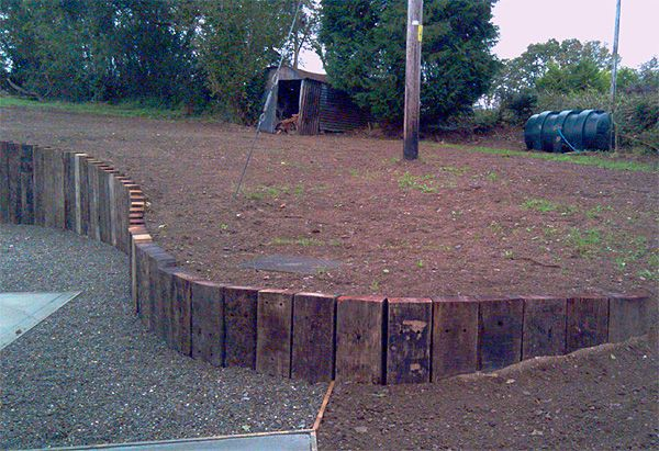 Curved retaining wall from railway sleepers on end for Curved garden wall ideas