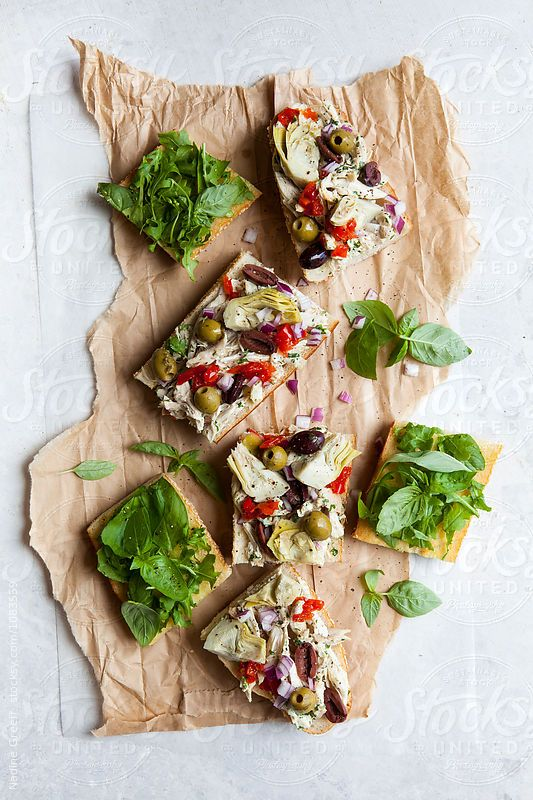 Chicken, artichoke, green olive and basil on ciabatta baguette by Nadine Greeff for Stocksy United