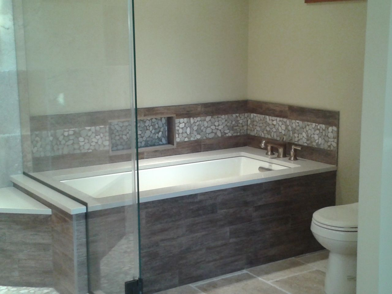 Wood tile with pebble tile border Tub is undermounted with a solid ...