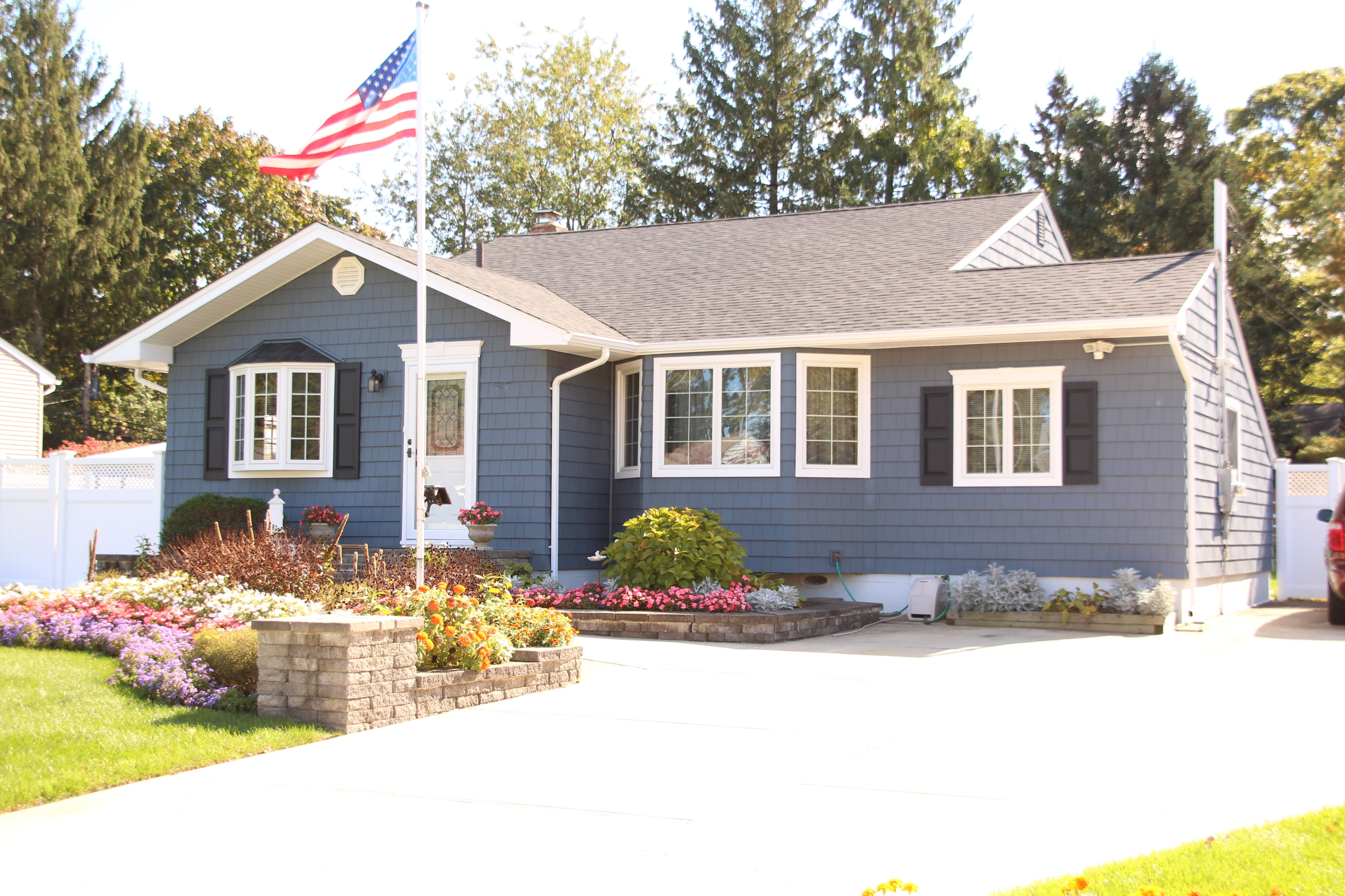This Modified Ranch Home Is Patriotic With Its Flag Pole And American Flag Yet Is Stoic With It S Blue Vinyl Ranch House Exterior Blue Siding Blue Vinyl Siding