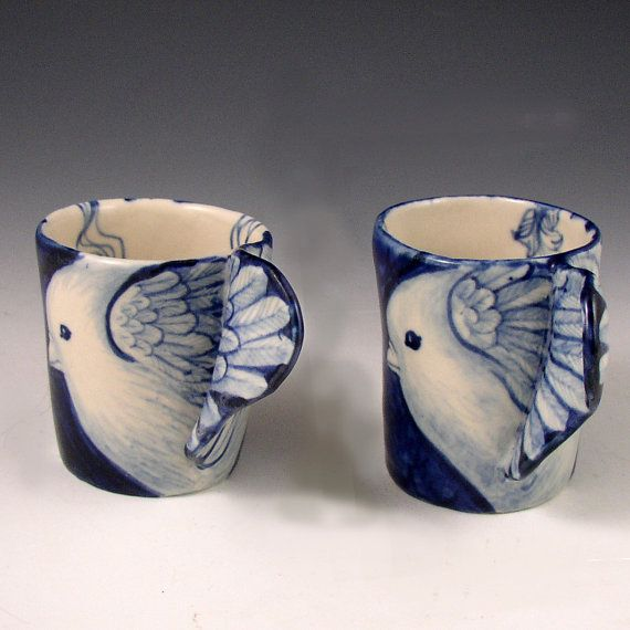 This is a pair of small hand formed and hand painted cups with bird wings as handles and ladies on the front of each. One is 2.6 tall and the other is 2.8 with a diameter of approx 3.5. They would make a wonderful gift alone or with a bottle of something delicious.
