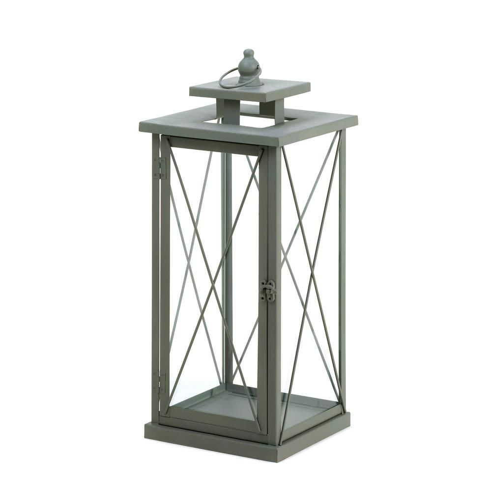 Make a big style statement with this stunning and unique candle lantern. Four glass panels are held by decorative metal framework and topped with a finial and hanging loop. Item weight: 4.4 lbs. 7 1/8 x 7 1/8 x 17 1/4 high; 18 1/4 high with handle. Iron and glass.