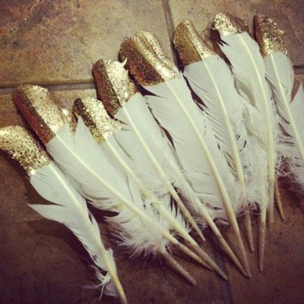 DIY Gold Glitter Feathers-  hmmm. Thinking to write names near (parallel) feather quill for place cards.   Or color code tips of feather with people...  I've never attempted to write on a feather!