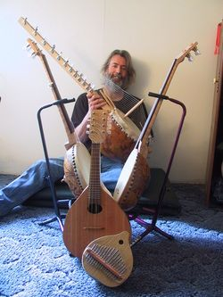 Patrick Loafman with his gourd musical instruments, including a gourd kalimba, gourd mandolin, 2 gourd banjos and a kora.