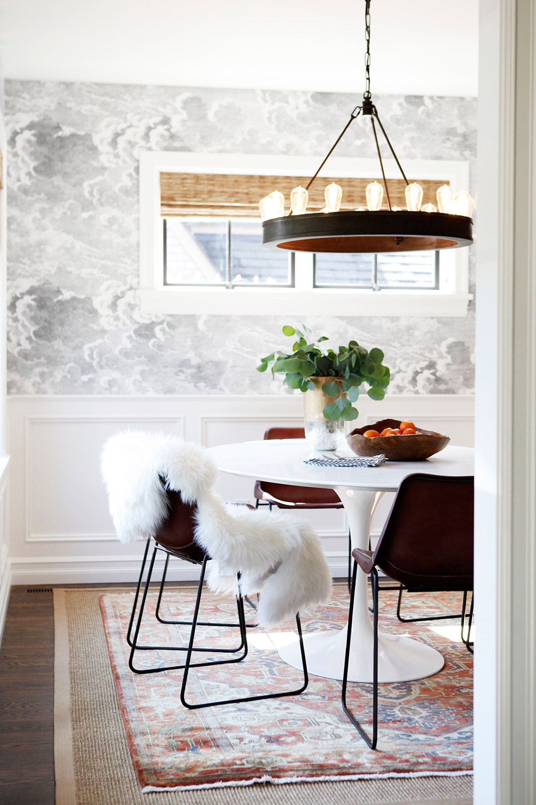 Modern Dining E With Sheepskin Rug On Black Chairs And Chandelier Exposed Light Bulbs