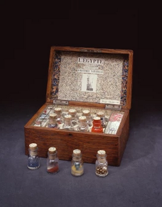 Joseph Cornell,L'Égypte de Mlle Cléo de Mérode cours élémentaire d'histoire naturelle,1940,Box construction including wood, paper, glass, sand, doll arm, wood ball, coin, mirror, cork, rock, plastic, thread, bone, rhinestones, sequins, beads, tulle, cut-outs, and glitter,11.9 x 27.1 x 18.4 cm (closed). Photography:Quicksilver Photographers, LLC. © The Joseph and Robert Cornell Memorial Foundation/VAGA, NY/DACS, London 2015.From royalacademy.org.uk.