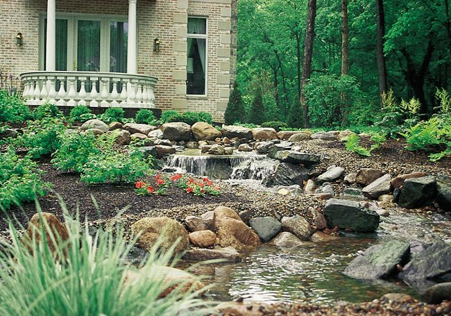 grand home receives winding stream in their expansive yard to help break up the space