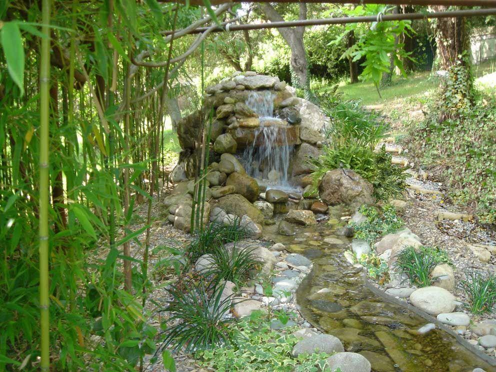 La cascada vuelca el agua al riachuelo estanque en for Cascada de agua para jardin