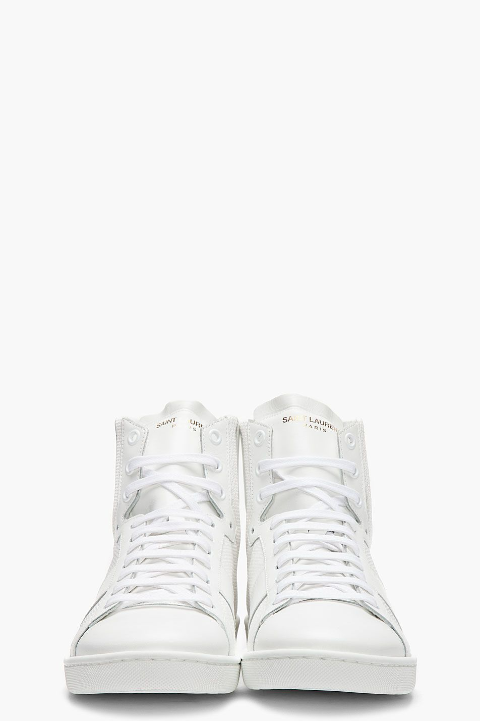 SAINT LAURENT //  White leather-paneled high-tops  32418M050006  Buffed leather high-top sneakers in white. Tonal textile panels. Round toe. Tonal lace-up closure. Logo stamp at padded tongue. Tonal logo stamp at heel collar. White rubber sole with textured sole walls. Tonal stitching. Upper: leather and textile. Lining: leather. Sole: rubber. Made in Italy.  $705 CAD
