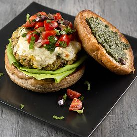 A Mediterranean inspired veggie burger with chickpeas and farro is topped with an olive tomato relish, warm feta, and pesto. Vegan patty.