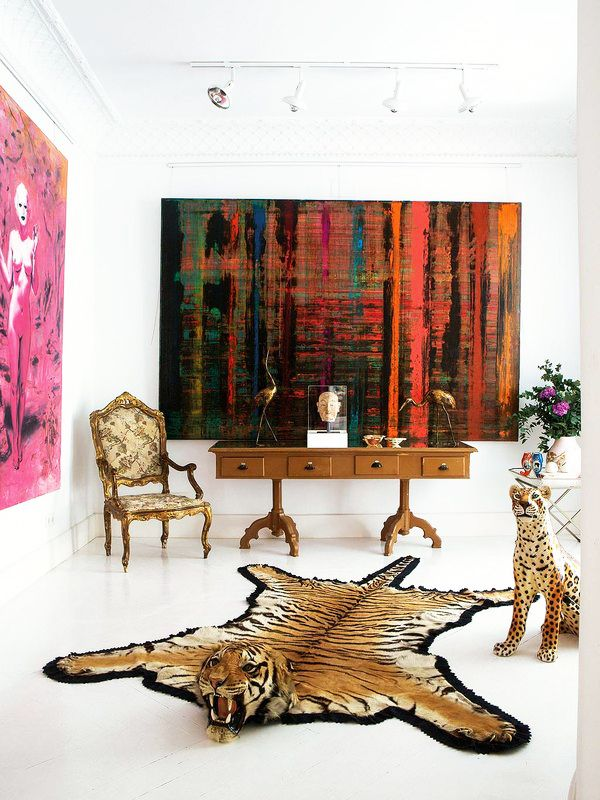 Abstract artwork in foyer with traditional armchair, faux tiger rug and antique console table