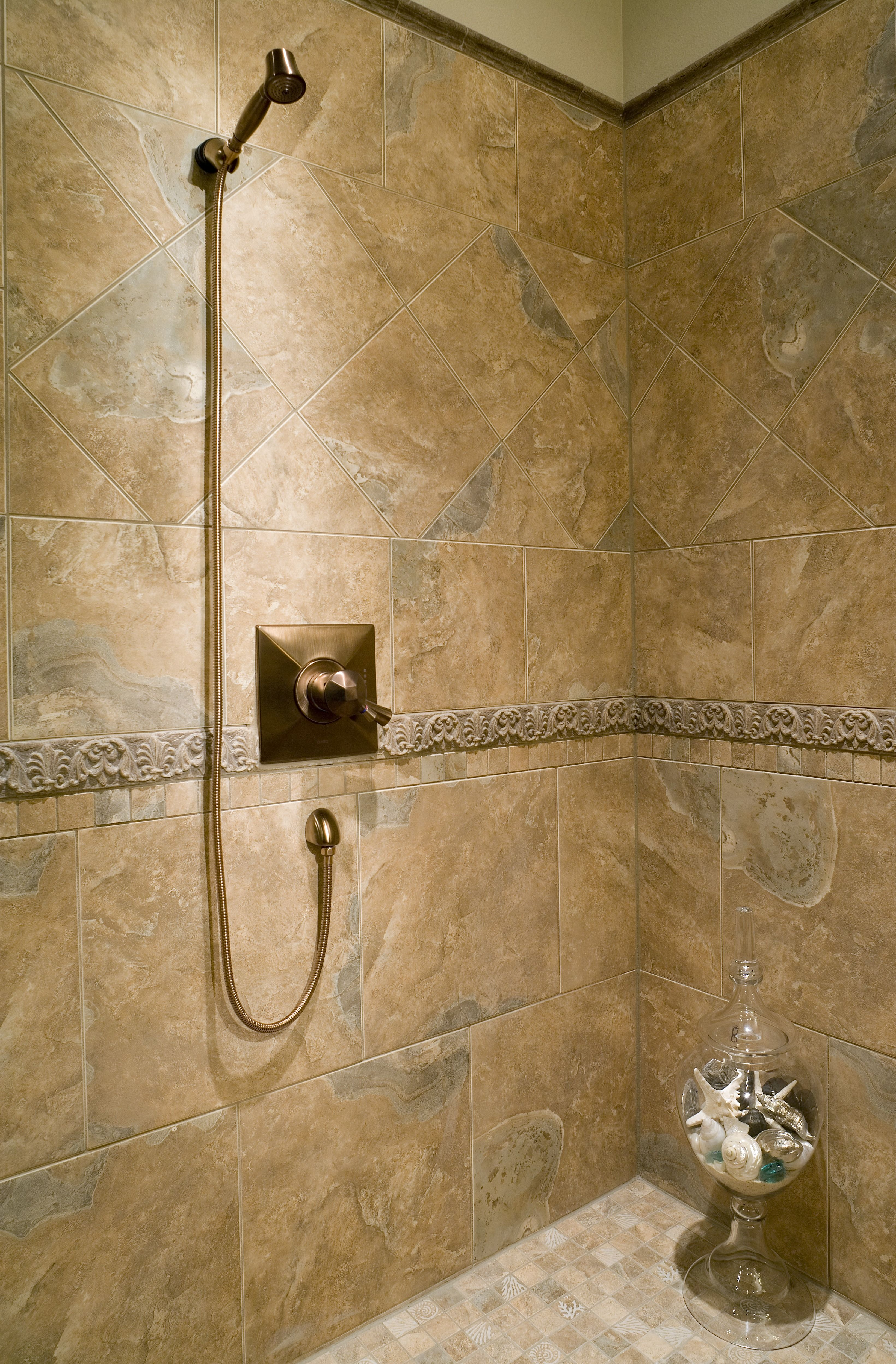 Light tan stone tile covers the walls of this shower. There is ...