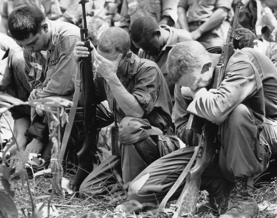 U.S. infantrymen pray in the Vietnamese jungle Dec. 9, 1965 during memorial services for comrades killed in the battle of the Michelin rubber plantation, 45 miles northwest of Saigon.