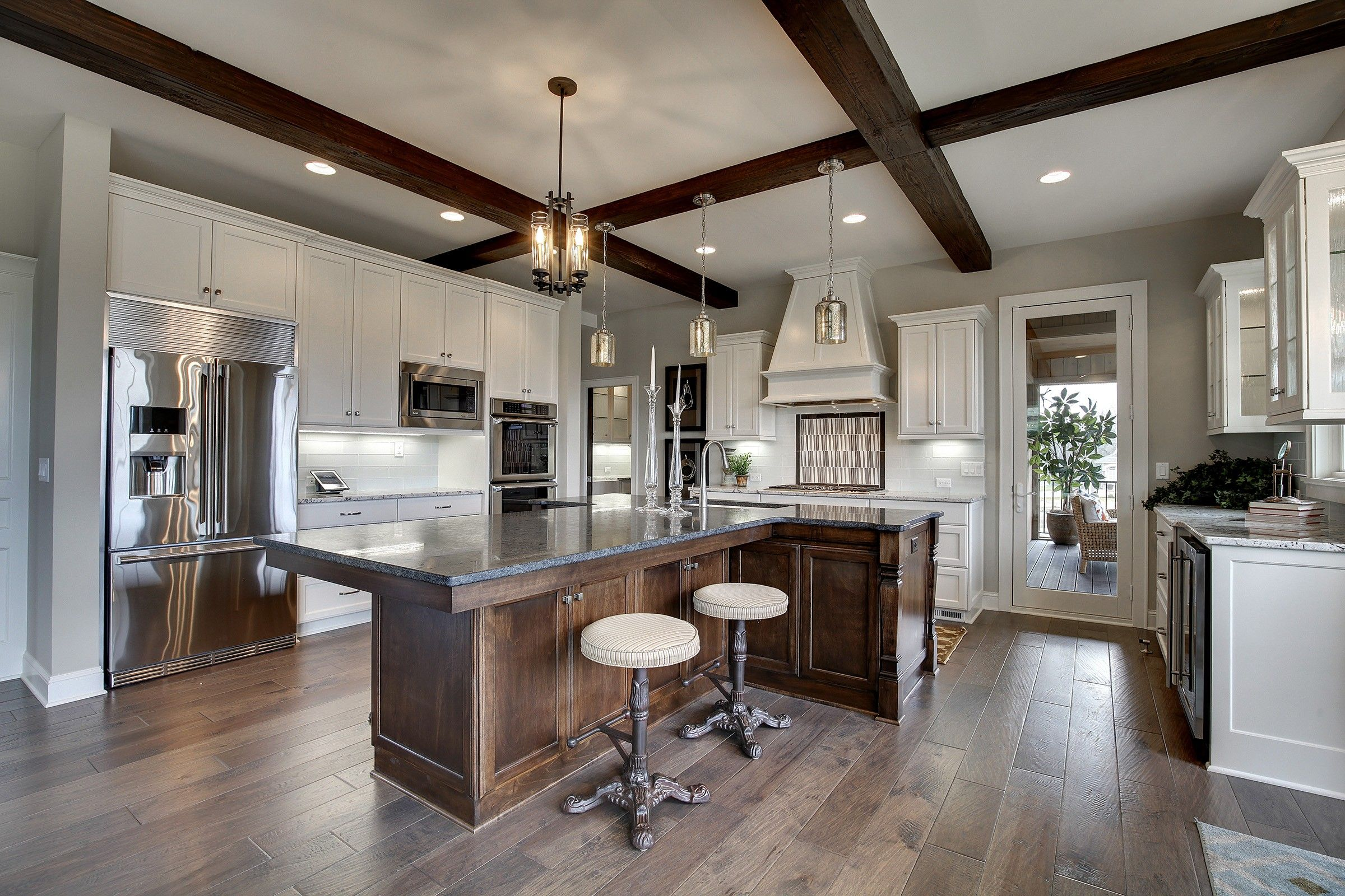 gourmet kitchen with exposed wood beams and white custom