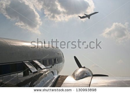 Vintage propeller airplane with modern jet overhead - stock photo