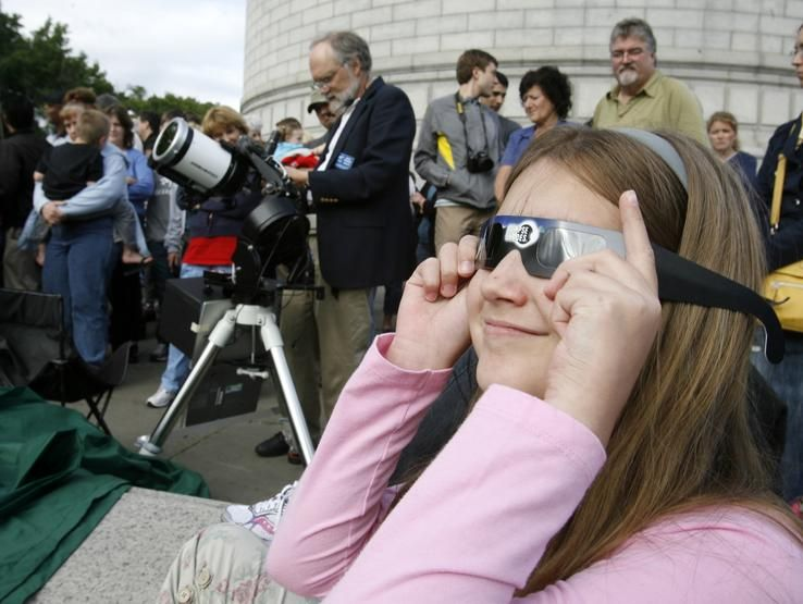 Olivia Mullet, 9, of Sugar Creek, used dark glasses to view the sun Tuesday. People gather at the McKinley Monument to watch Venus' transit across the sun.