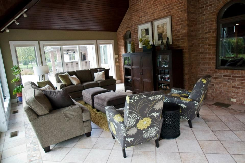 Beaded stained ceiling. Brick walls. Tile flooring. Gray Sofa. Flowered chair #modernsunroom