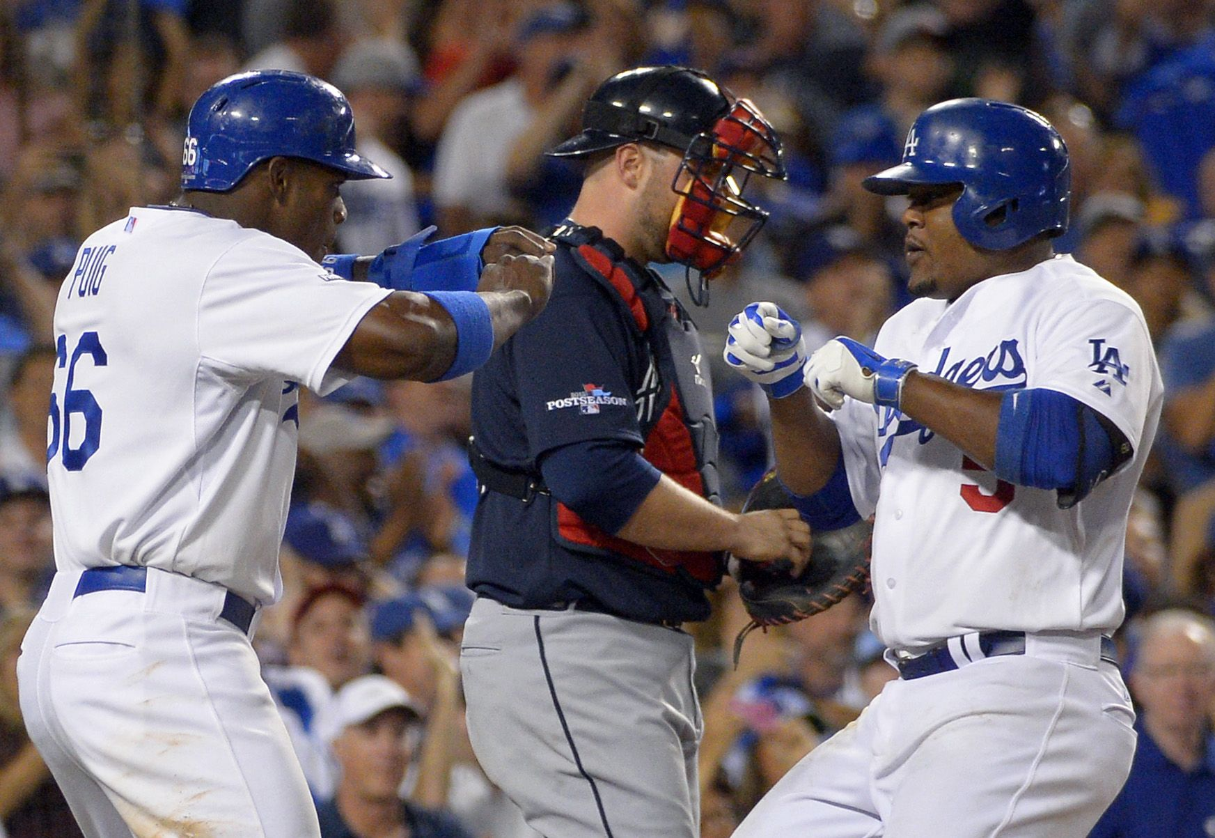 Los Angeles Dodgers Juan Uribe Right Greets Dodgers Yasiel Puig Left At The Plate Next To Atlanta Braves Catcher Brian Mccann Center After Uribe Hit A T