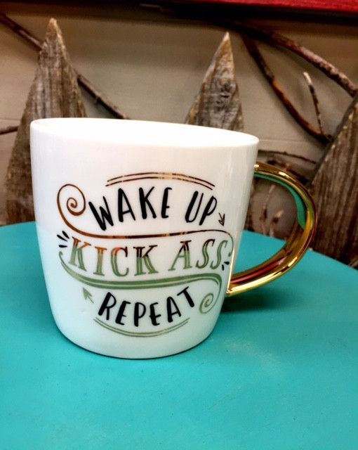 "Ceramic mug with ""Wake up kick ass repeat"" sentiment with metallic paint. Gold metallic handle. Dishwasher safe, do not microwave."
