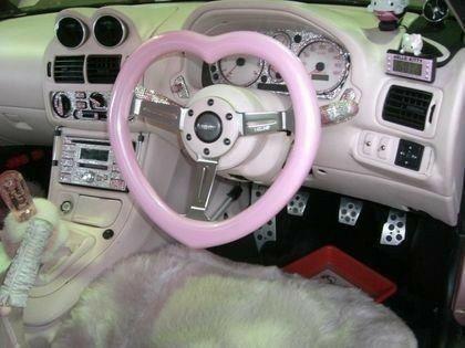 Girly car interior and a pink heart shaped wheel
