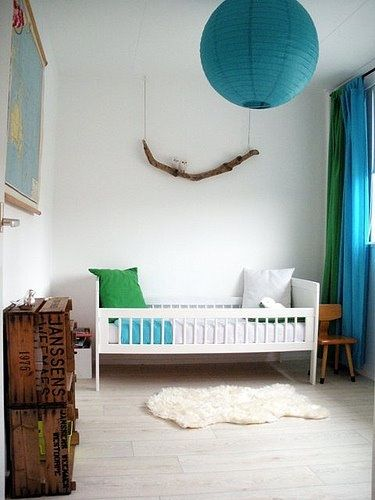 Woodland themed nursery in subtle shades of white with bold turquoise/aqua and leafy green. Natural wool and white furnishings keep the area crisp and uncluttered while offering a stimulating visual experience.