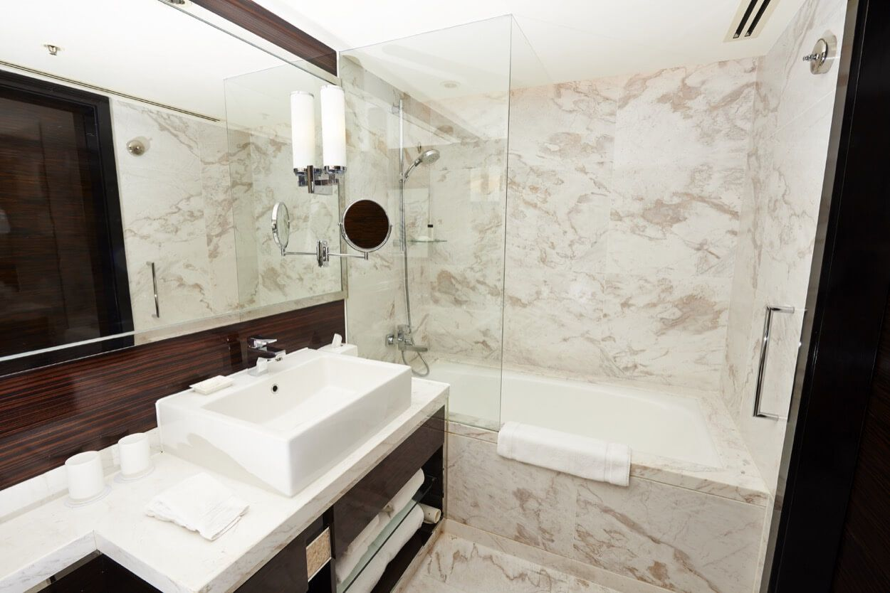 Fully Tiled Bathroom With Wooden Vanity And Single Sink | Renovate ...