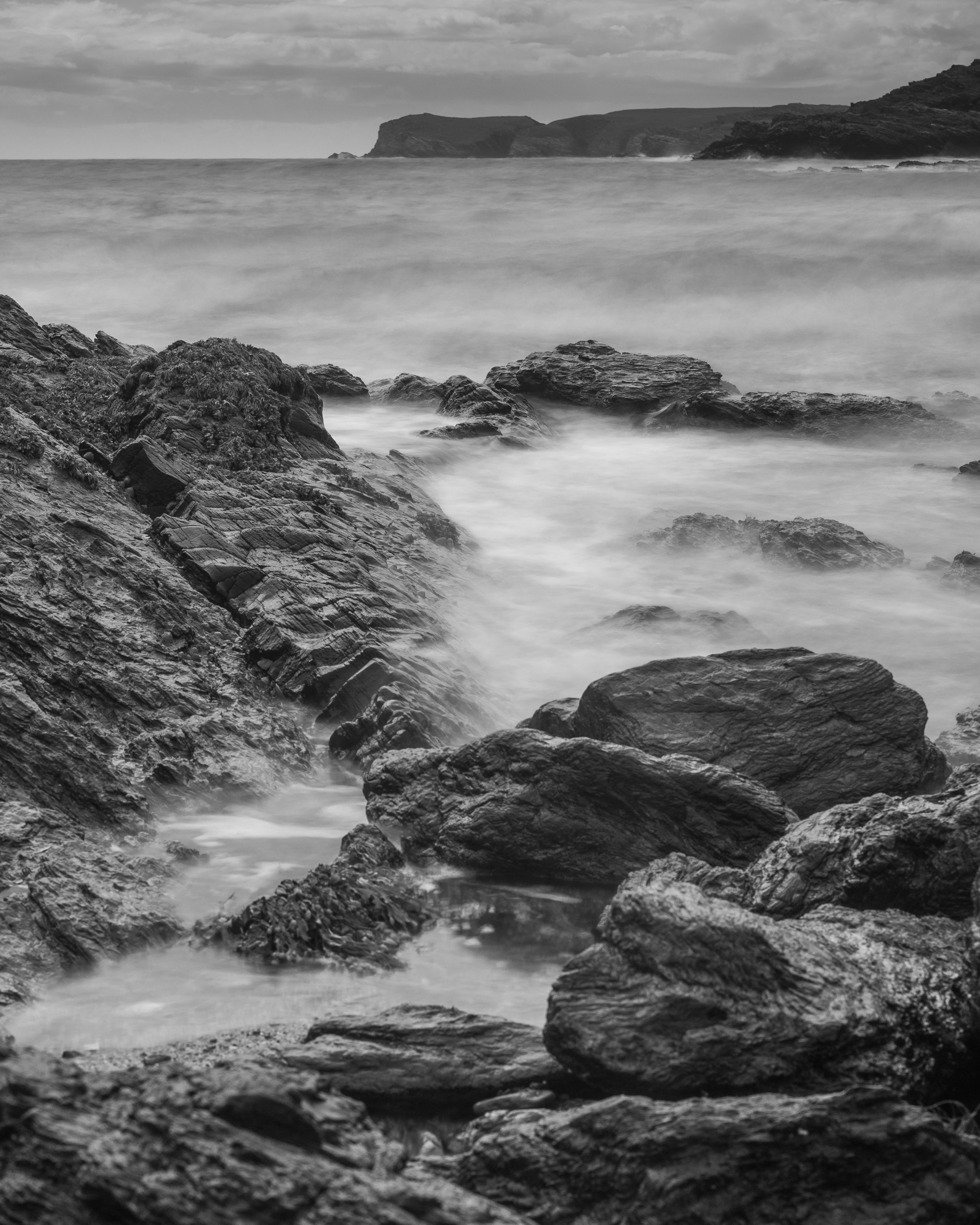 Water smooth over rocks in this black and white seascape photograph