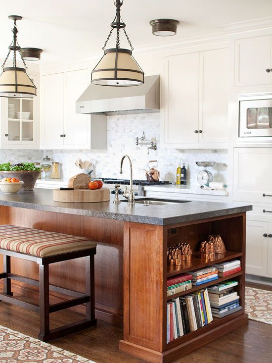 The island and cabinets in this kitchen share a clean and simple style. The dark wood of the island pops against the creamy white backdrop.