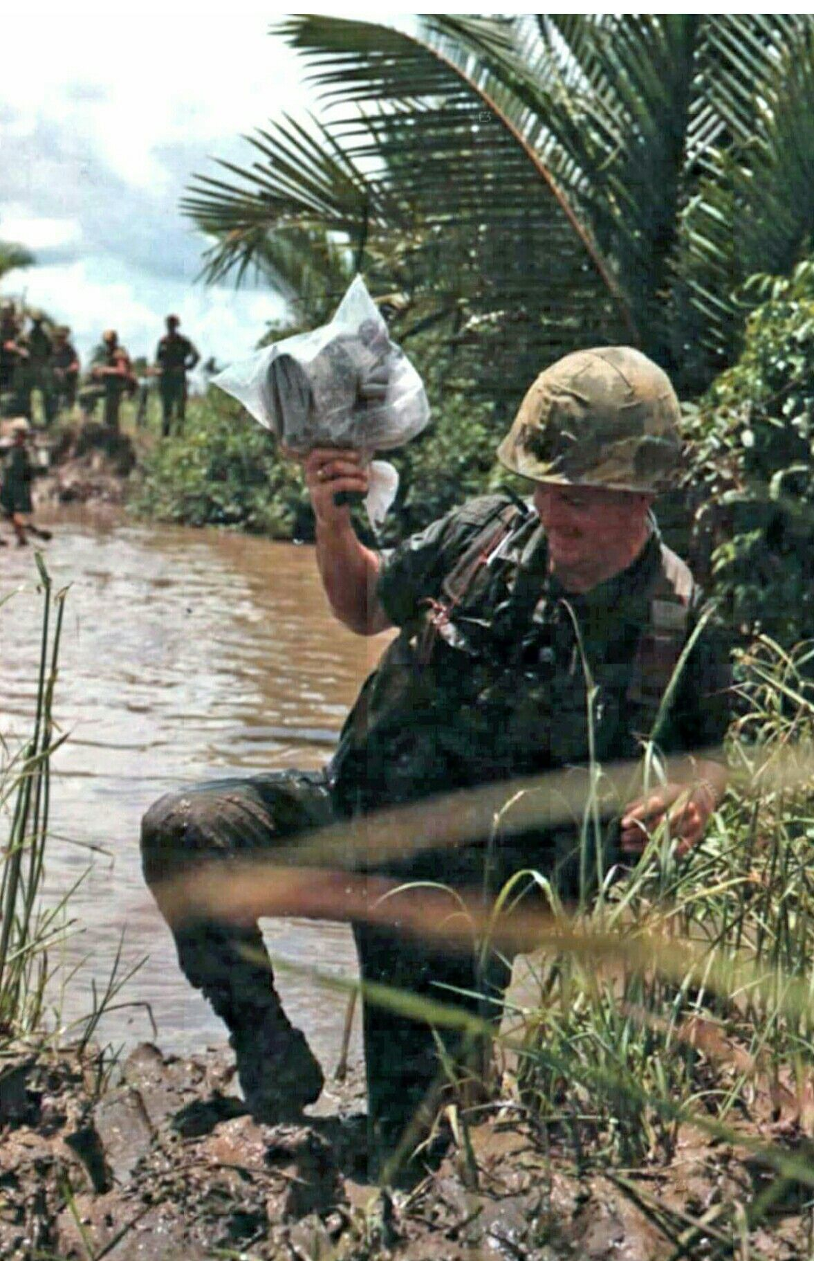 Sgt Thomas O. Wade, DASPO photographer, climbs a muddy bank after crossing a small river while covering Operation Fairfax and Company A, 4th Bn, 12th Inf, 199th Inf Bde, near Saigon, 7 May 67. His camera is wrapped in a plastic bag to keep it dry.