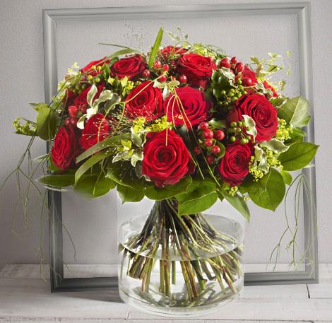 Elixir Rouge : Bouquet rond généreux de roses gros boutons rouges avec un délicat travail de feuillage.