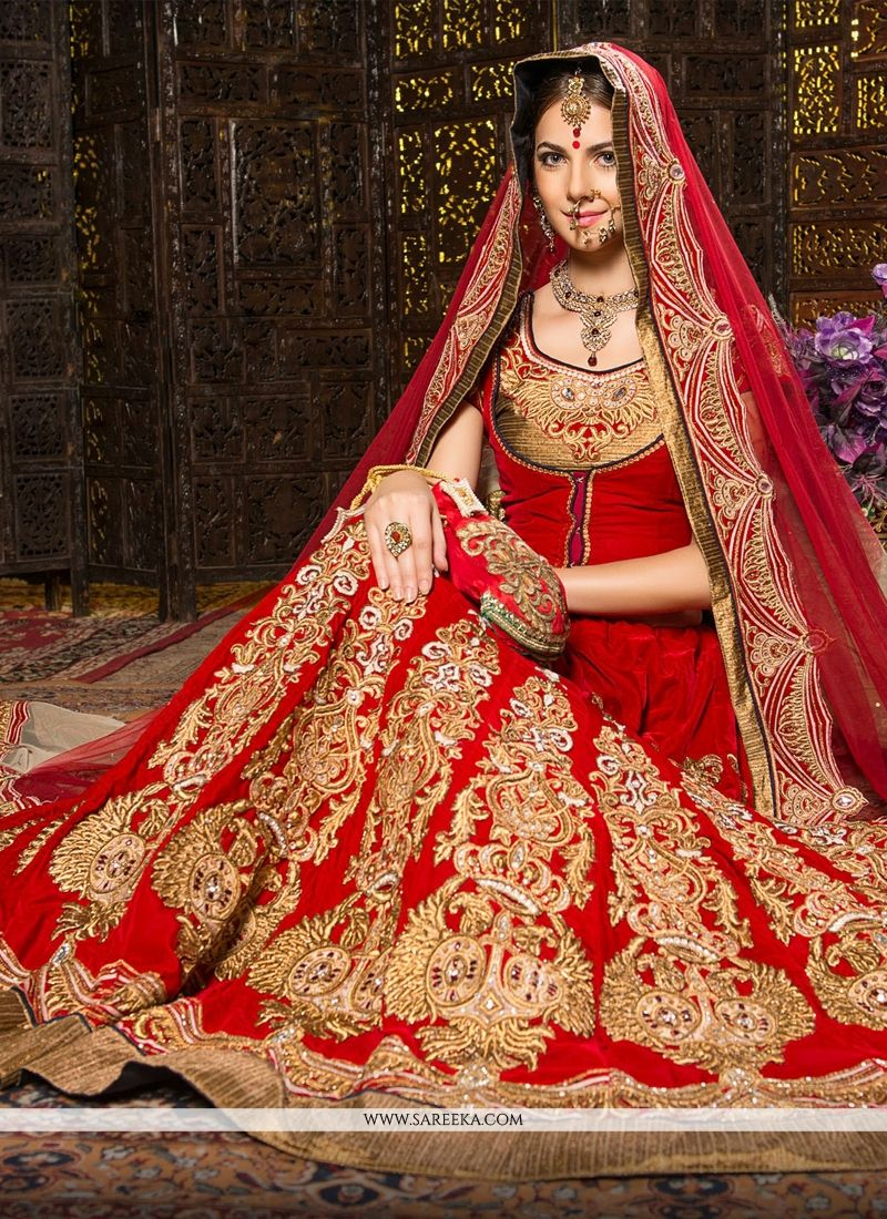 Fab red velvet wedding lehenga choli designed with zari, embroidery, stone and patch border. Available with un-stitched choli fabric which can be customized as per your style or pattern. choli shown i...