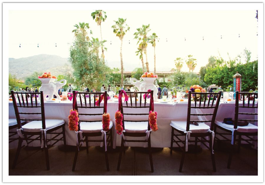 Vibrant blooms dangling from the Bride & Groom's chairs in this modern Moroccan wedding by Alchemy Fine Events