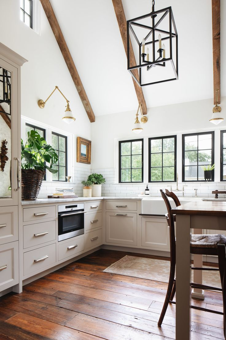 Kitchen with white walls, reclaimed barn wood beams, sconces, antique brass, dark window panes,…